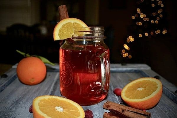 Cranberry Cider in a Mug Next to Fresh Oranges, Cranberries and Cinnamon Sticks